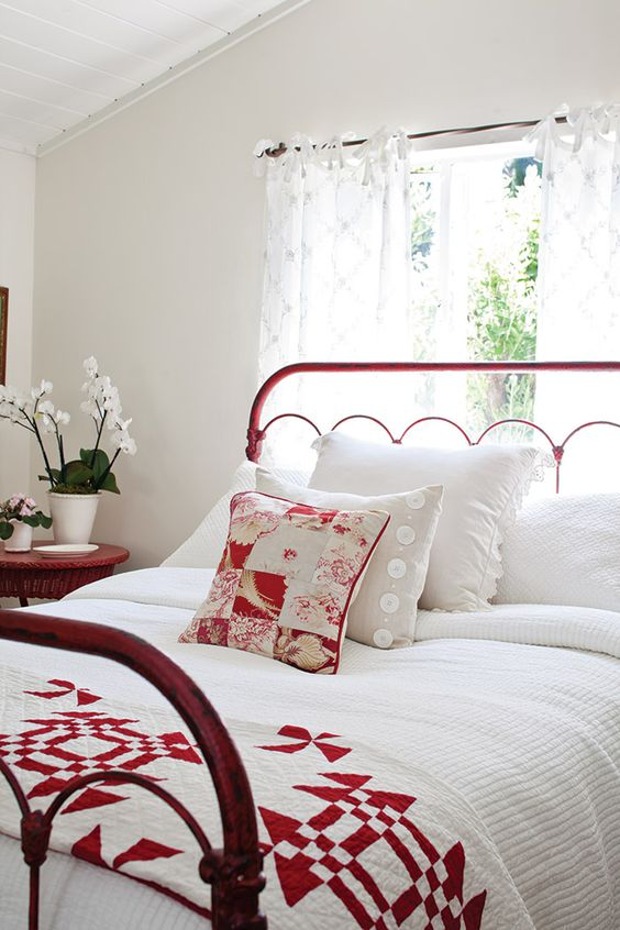 white bedroom with red metal bed frame and quilt at the foot of the bed